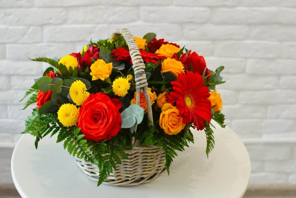 A bouquet of flowers using red roses, red margaritas, and yellow chrysanthemums