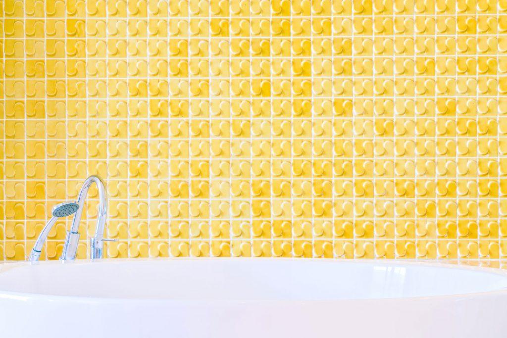 A bright yellow colored bathtub backsplash