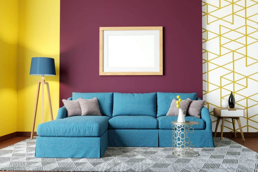 A classic designed living room with a burgundy colored accent wall, blue sectional sofa, and a black and white patterned carpet