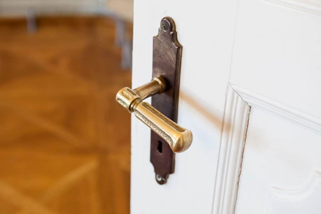 A classic styled brass handle door knob installed in a white door