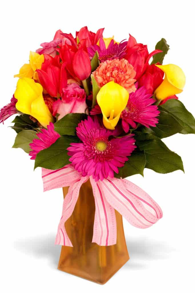 A colorful flower arrangement using striped bow pink flowers on a brown glass vase on a white background