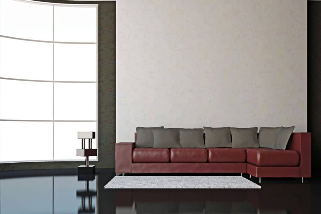 A dark burgundy colored sectional sofa with gray throw pillows inside a huge living room