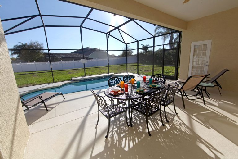 A huge stucco walled lanai with metal dining chairs and a small pool near the window, 21 Great Screened Lanai Ideas