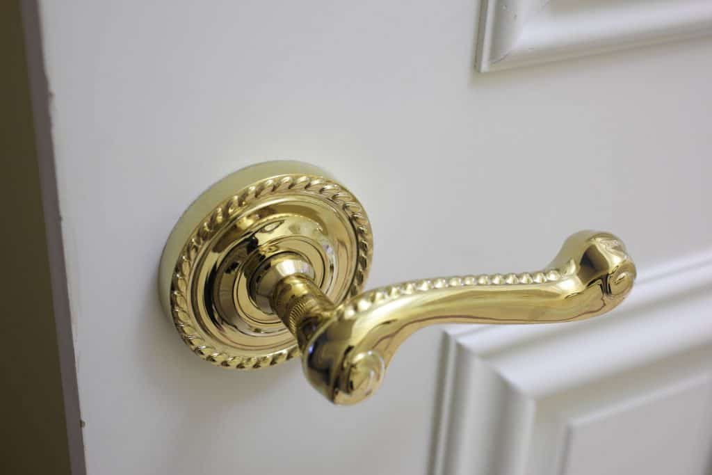A luxurious gold plated door handle installed in a white door