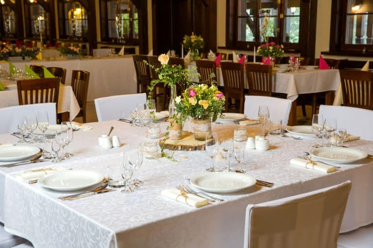 A luxurious restaurant incorporated with white clothing and wooden chairs, How To Choose A Tablecloth Color - Questions To Ask Yourself
