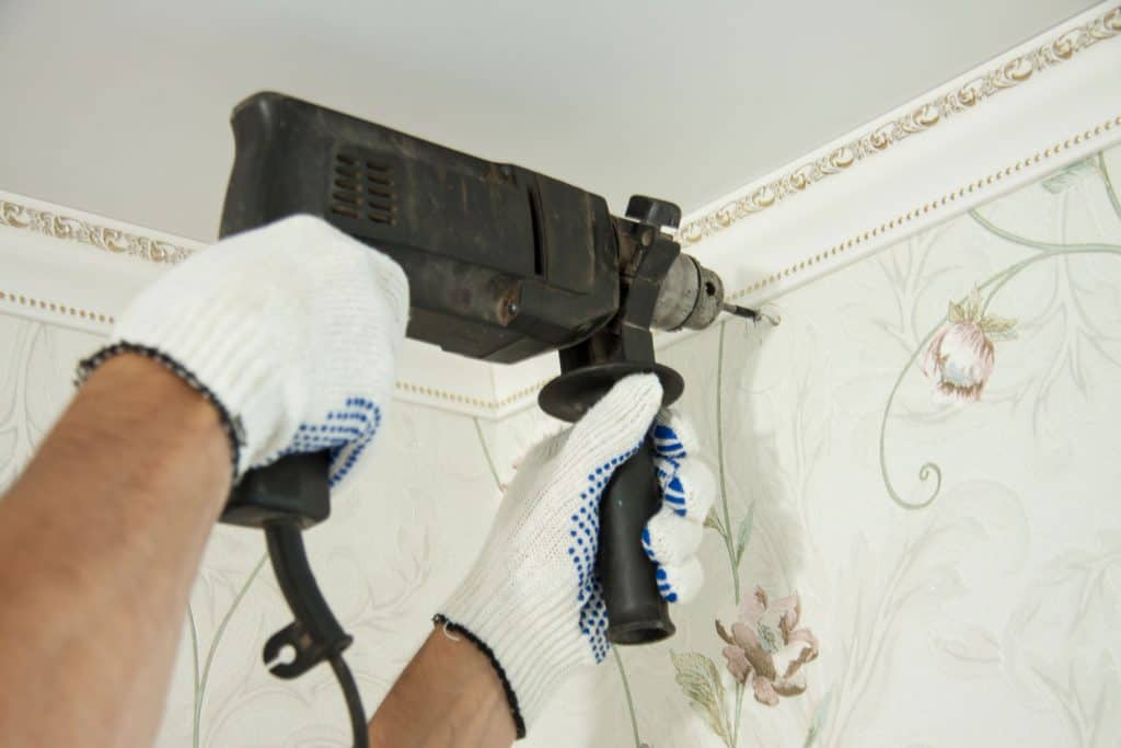 A man drilling the wall for screw mount for the curtains rods