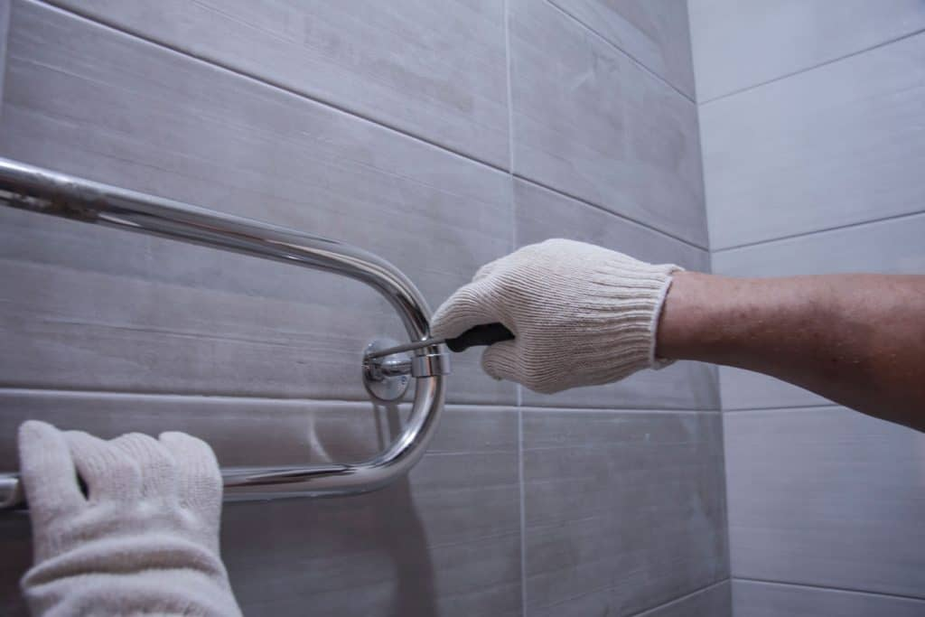 A worker installing a stainless steel handle bar