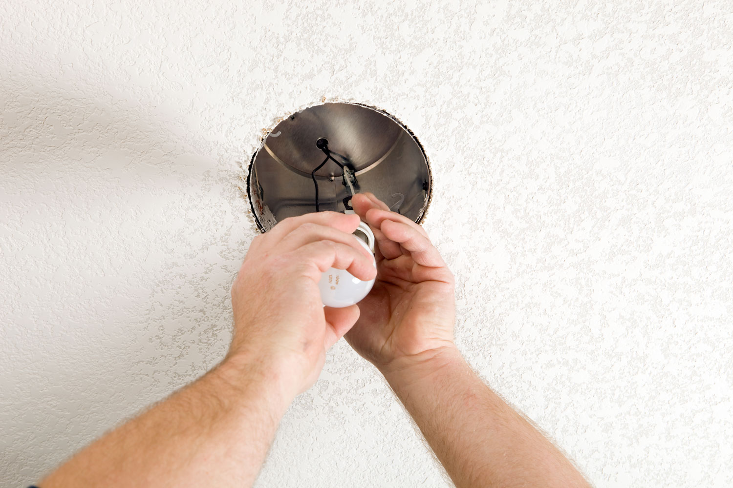 A man installing a 100W light for the recessed lighting, How To Remove Old Recessed Lighting Cans