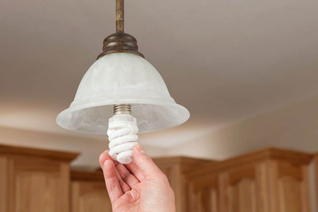 A man replacing a dangling lamp with a new incandescent bulb