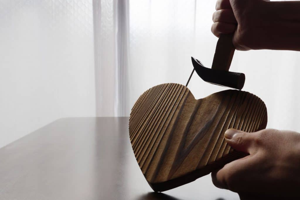 A man using a hammer to remove a nail from a heart carved workpiece