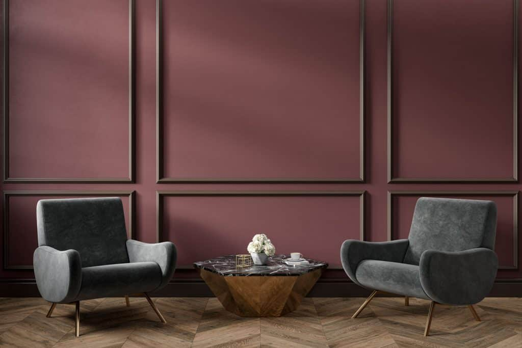 A modern burgundy living room with gray arm chairs and a coffee table complementing the wooden floor