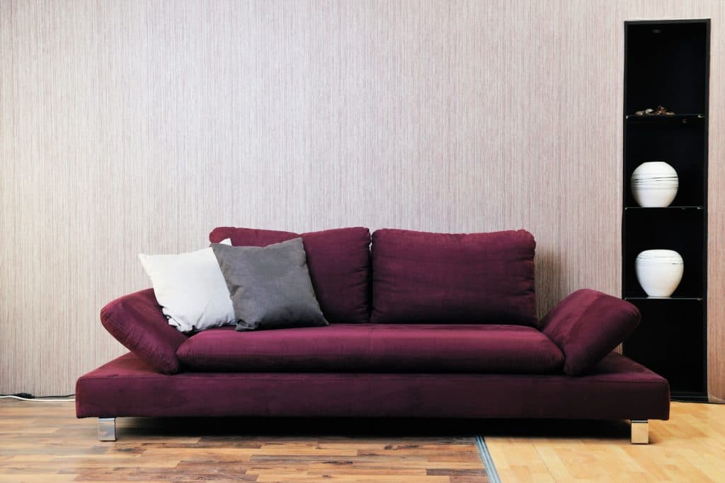 A modern designed burgundy colored sofa with gray and white colored throw pillows