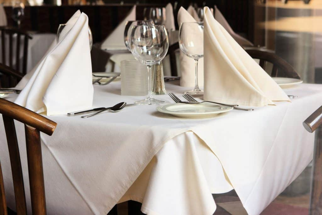 A neatly folded table napkins and white tablecloths inside a luxurious restaurant