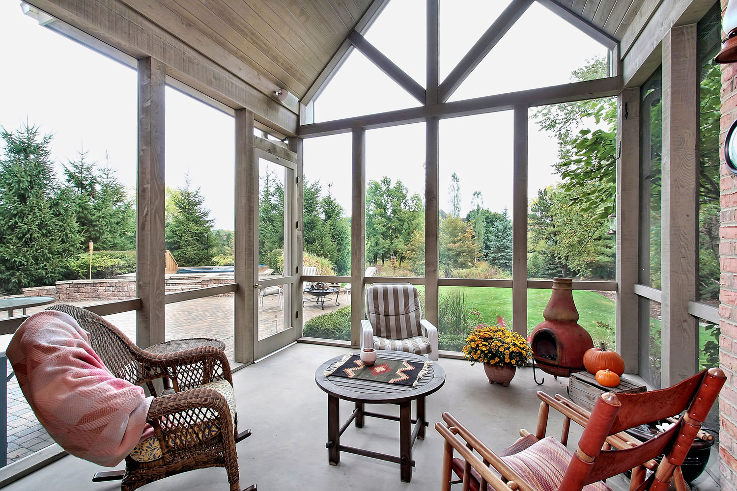 A screen porch design with wooden and rattan chairs