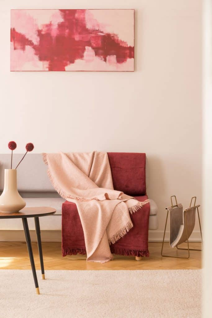 A small burgundy colored drape on top of a gray sofa and a small coffee table decorated with flowers