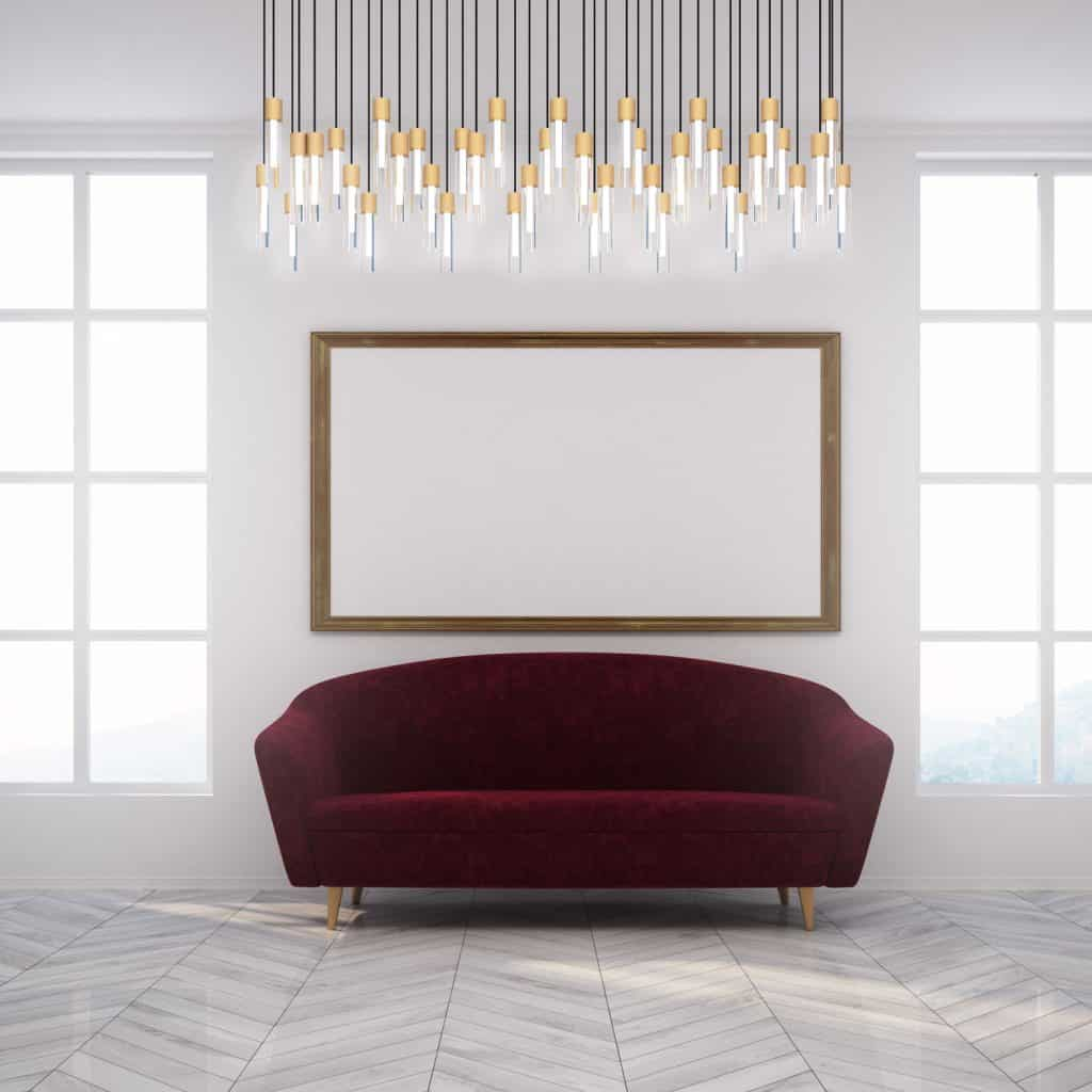 A small curved sofa inside a white color inspired living room with gorgeous dangling lights