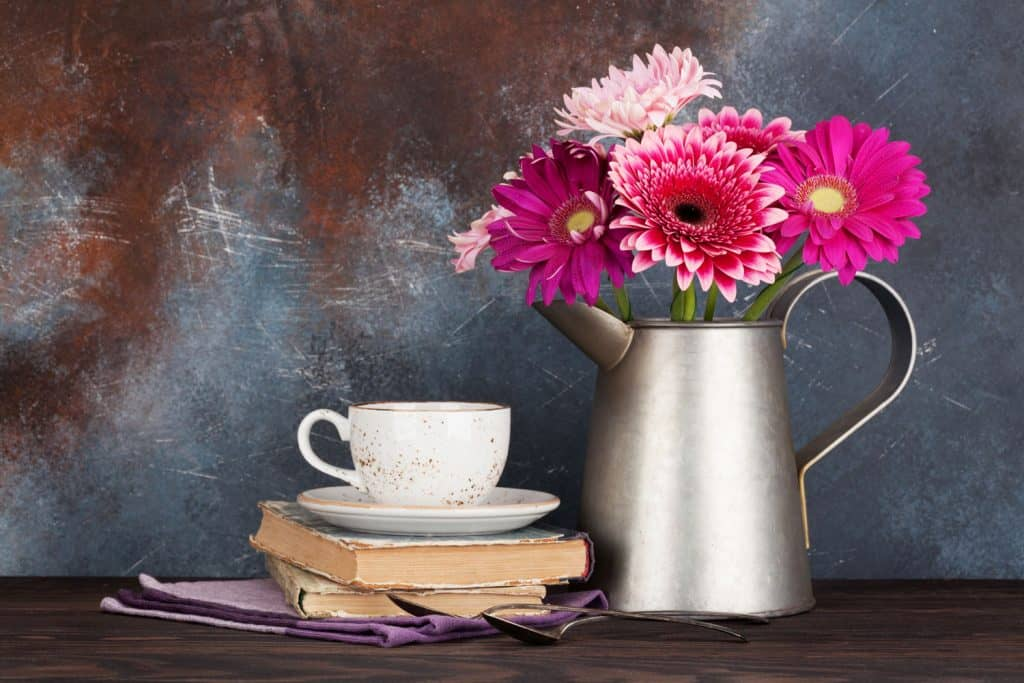A small stainless steel kettle decorated with pink gerbera flowers on a table