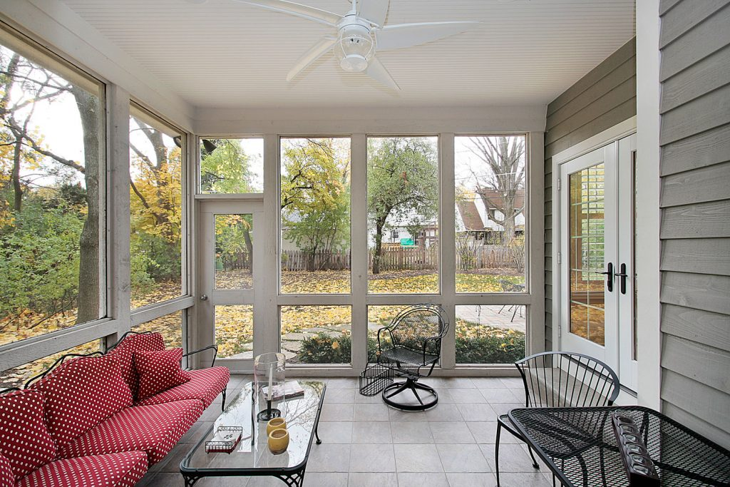 A spacious screen lanai with wooden framing and metal chairs on the side