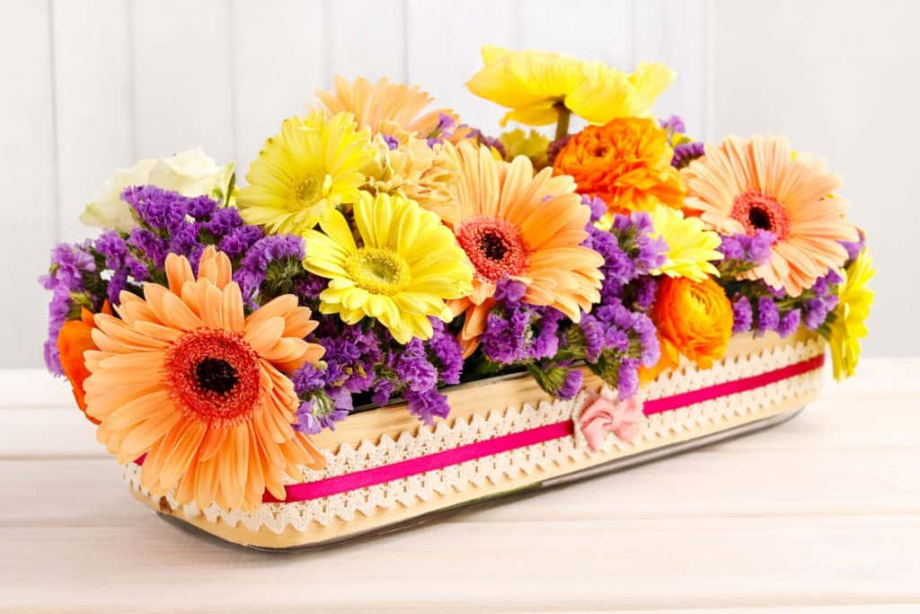 A stunning set of Gerbera flowers perfectly arranged on a small weaved tray