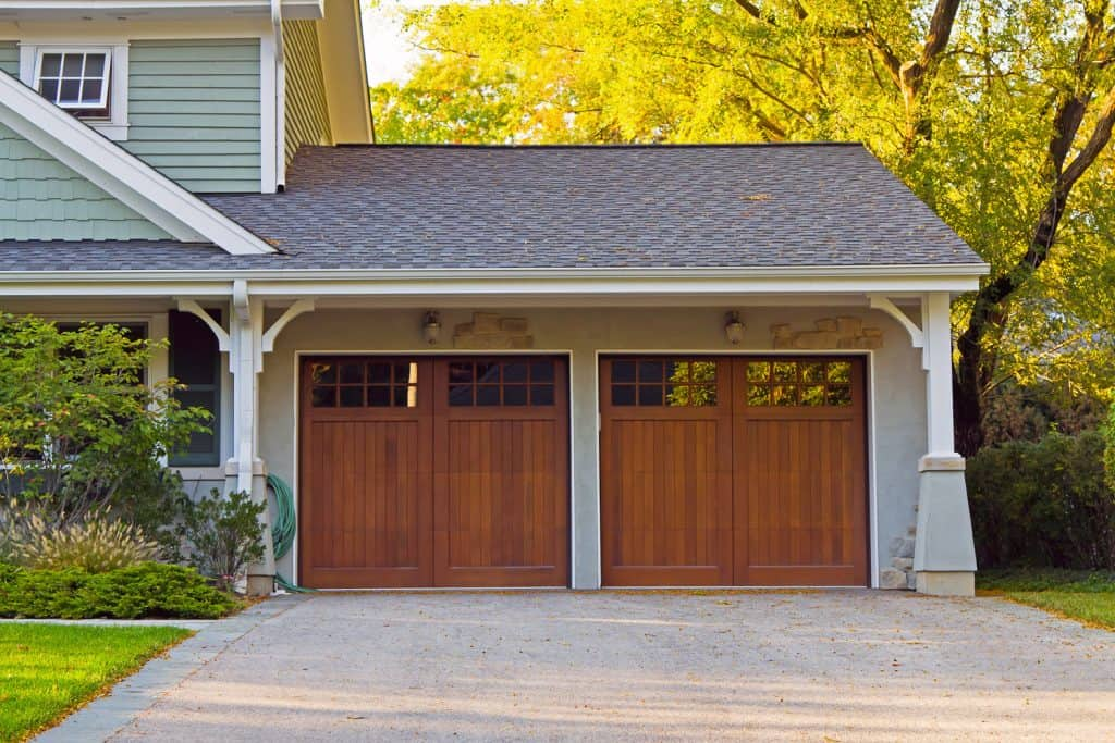 A two wooden garage door with small window and a two storey house, Should A Garage Have Windows?
