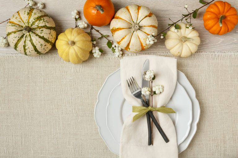 A white burlap table runner decorated with a plate and pumpkins on the table, How To Wash A Burlap Table Runner - 2 Methods