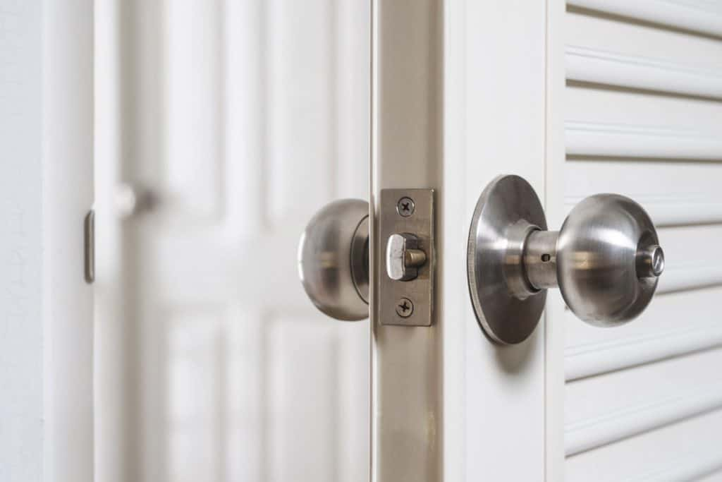 A white colored front door with a stainless steel door knob