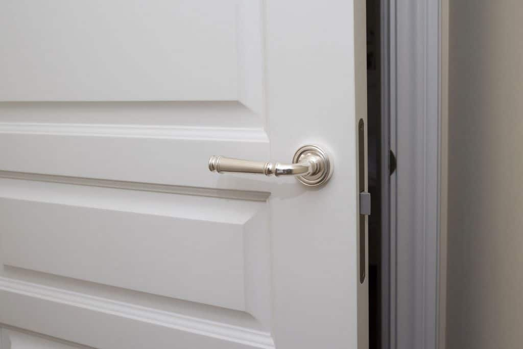 A white door knob with stainless steel door knob