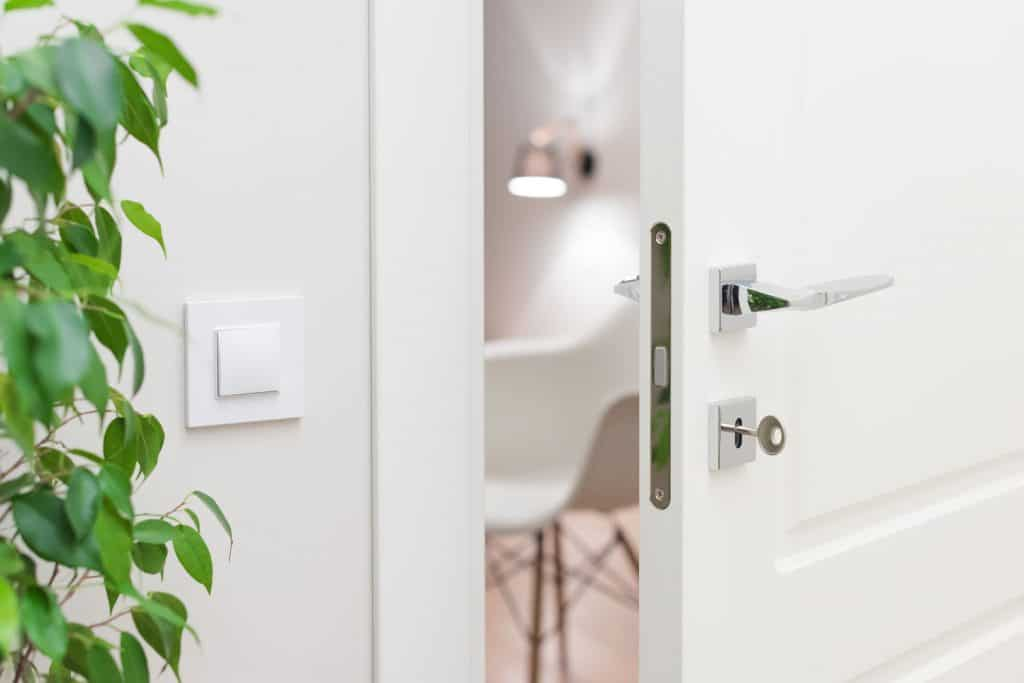 A white living room with a stainless steel modern door knob