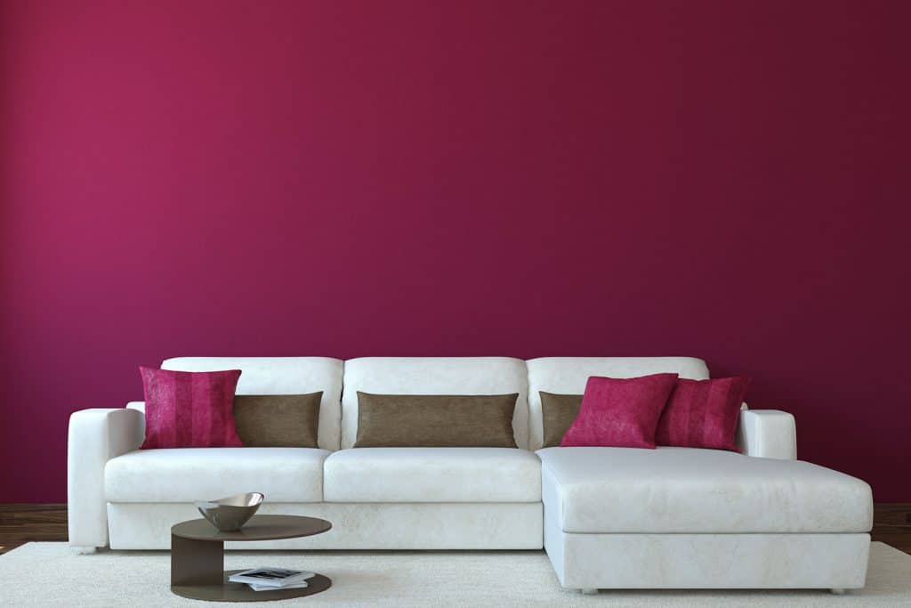 A white sectional sectional sofa with a white carpet inside a burgundy colored living room