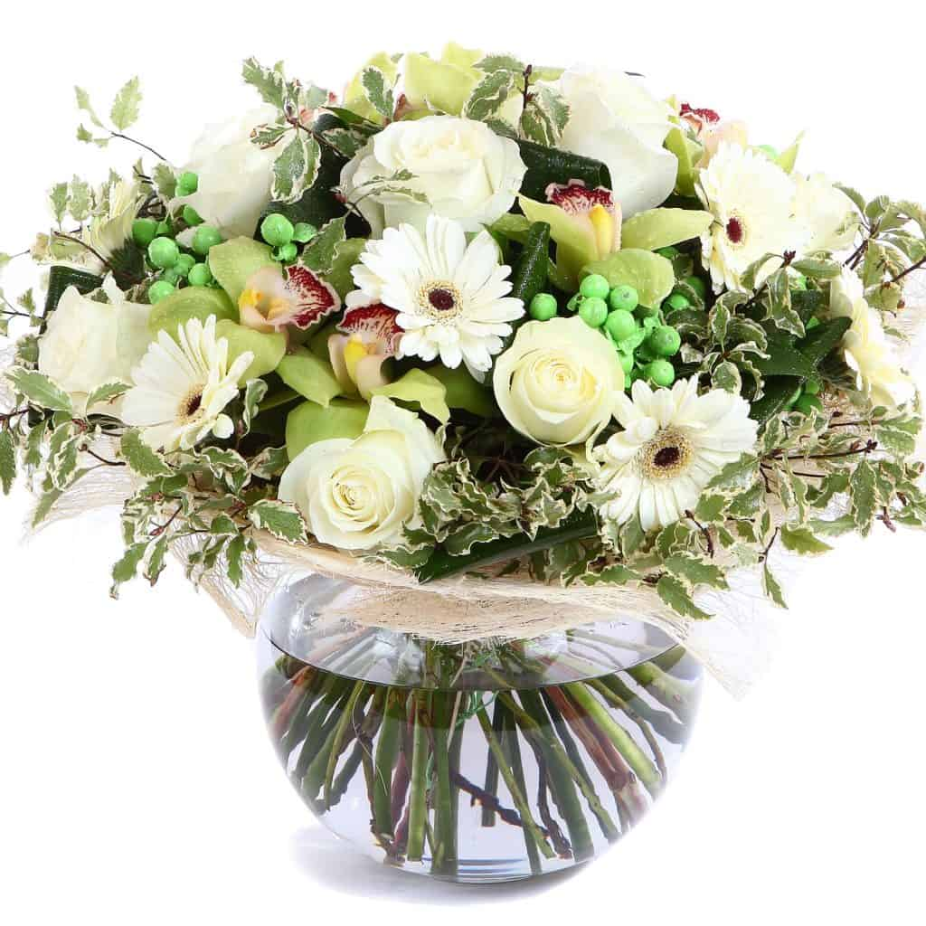 An elegant arrangement of gerbera flowers, green peas, and other variegated leaves on a glass vase
