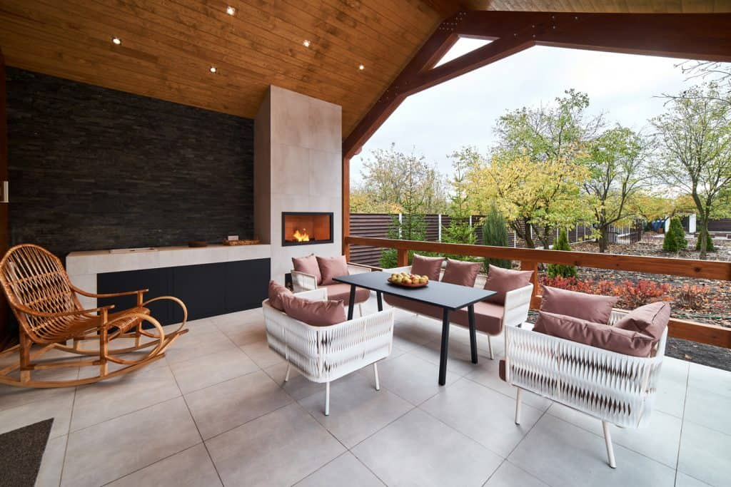 An open terrace with table, chairs, fireplace and apples. nobody