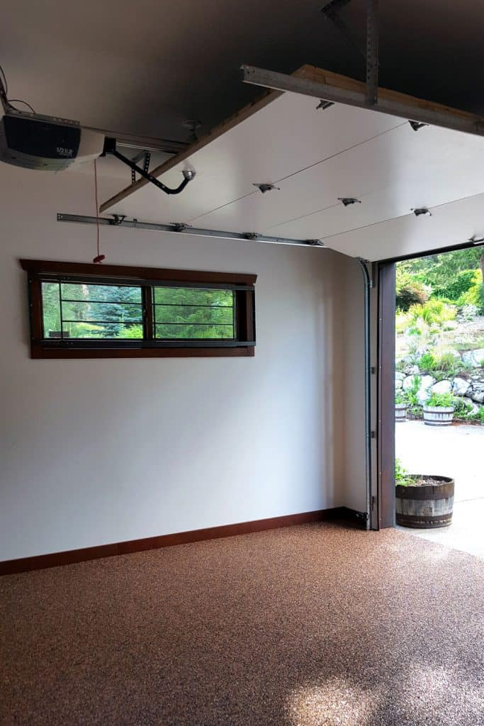 An opened garage door with a small bay window and a granite type flooring
