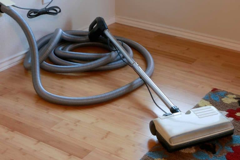 Bamboo hardwood floor and wool rug with a central vacuum cleaner attached to the wall, How To Unclog And Clean A Central Vacuum System [A Complete Guide]