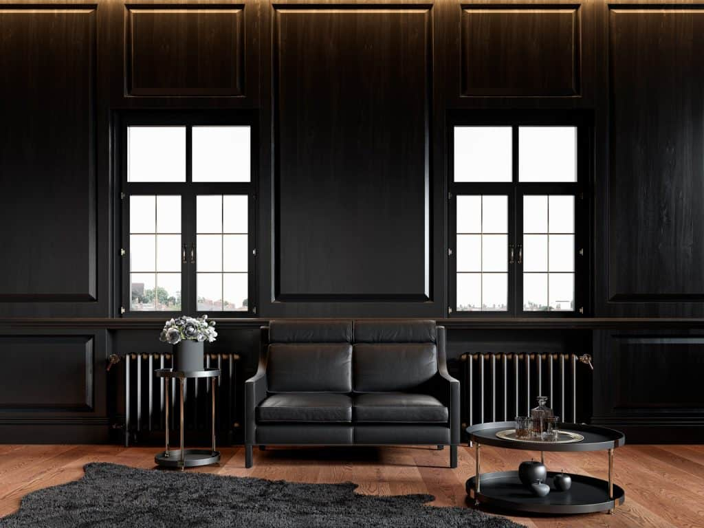 Black classic loft interior with wall panels, leather sofa, carpet and decor