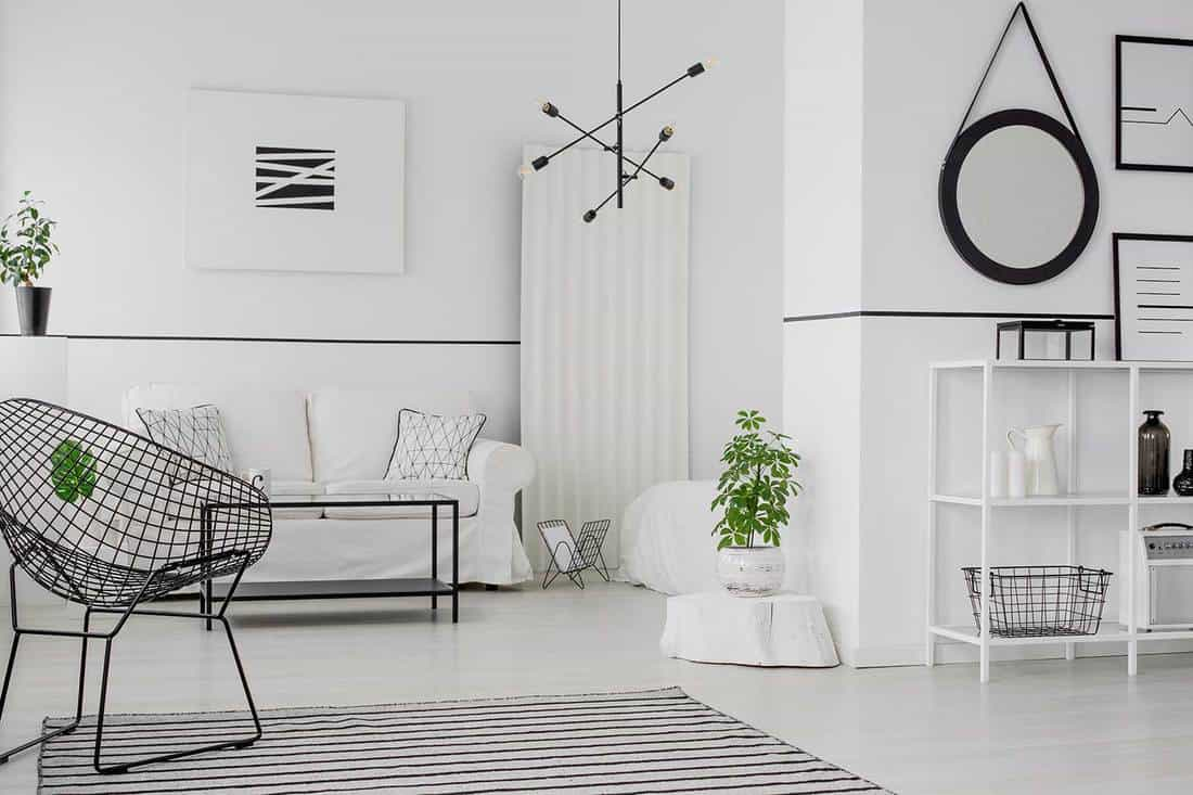 Black round frame on the wall in modern living room interior with armchair near white couch