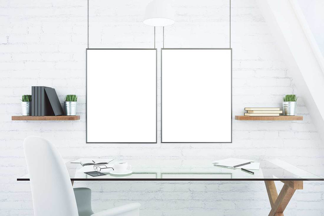 Blank white picture frames on brick wall in modern office with glassy table