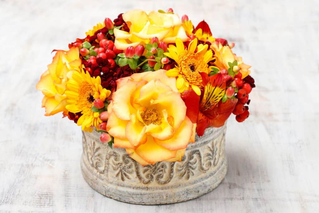 Bouquet of orange and red roses on a banquet table perfectly arranged on a vintage vase
