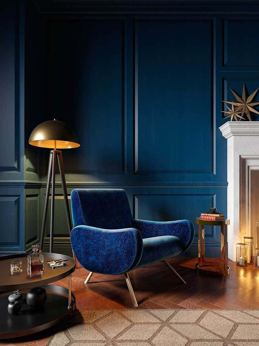 Classic royal blue color interior with armchair, fireplace, candle, floor lamp and carpet