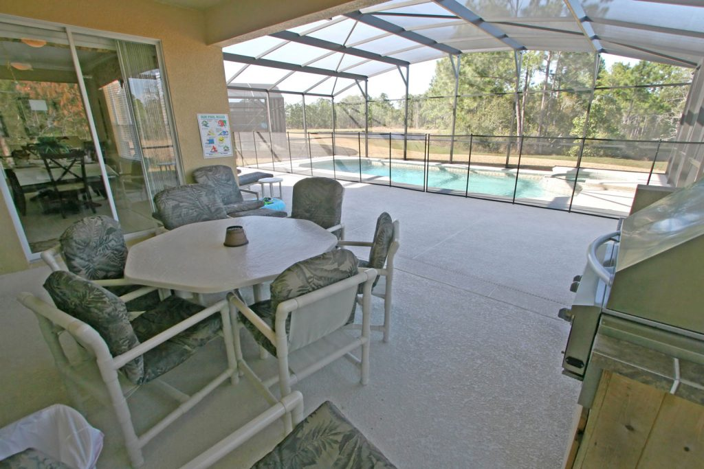 Contemporary inspired lanai with gray chairs on the screen designed lanai and a large pool on the side