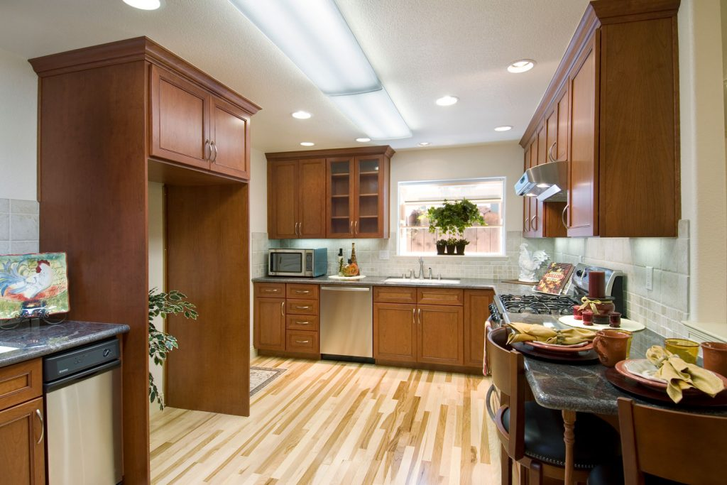 Contemporary modern kitchen with wooden flooring, wooden cabinetry, and recessed lighting