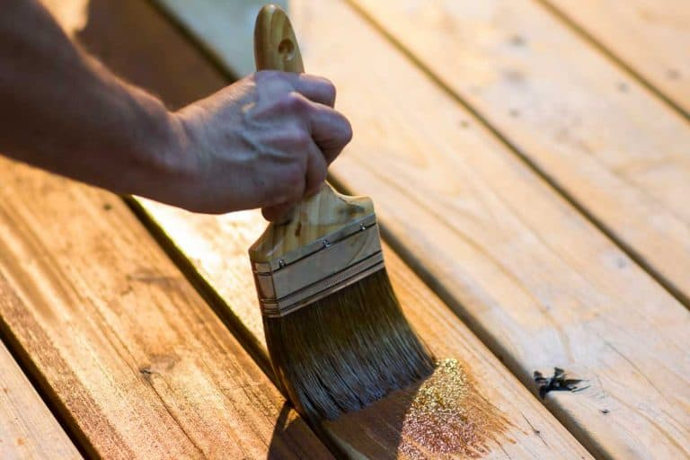 Cropped view of male carpenter applying stain to wooden furniture, Does Wood Stain Protect Wood?