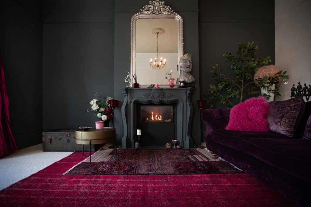 Dark inspired living room with a burgundy colored carpet, a dark painted fireplace mantel, and a dark sofa