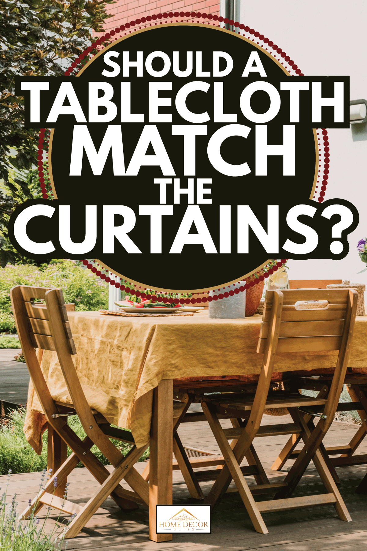 Dining table covered with orange tablecloth standing on wooden terrace in green garden. Should A Tablecloth Match The Curtains