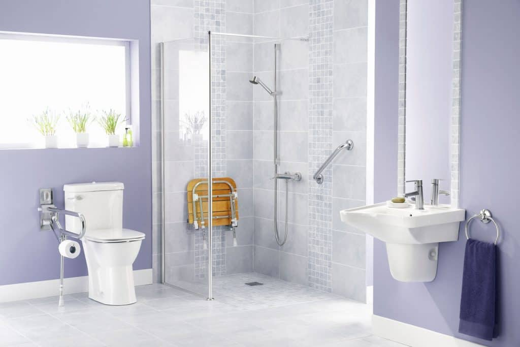 Elegant interior of a purple themed bathroom with glass walled shower area and a white toilet