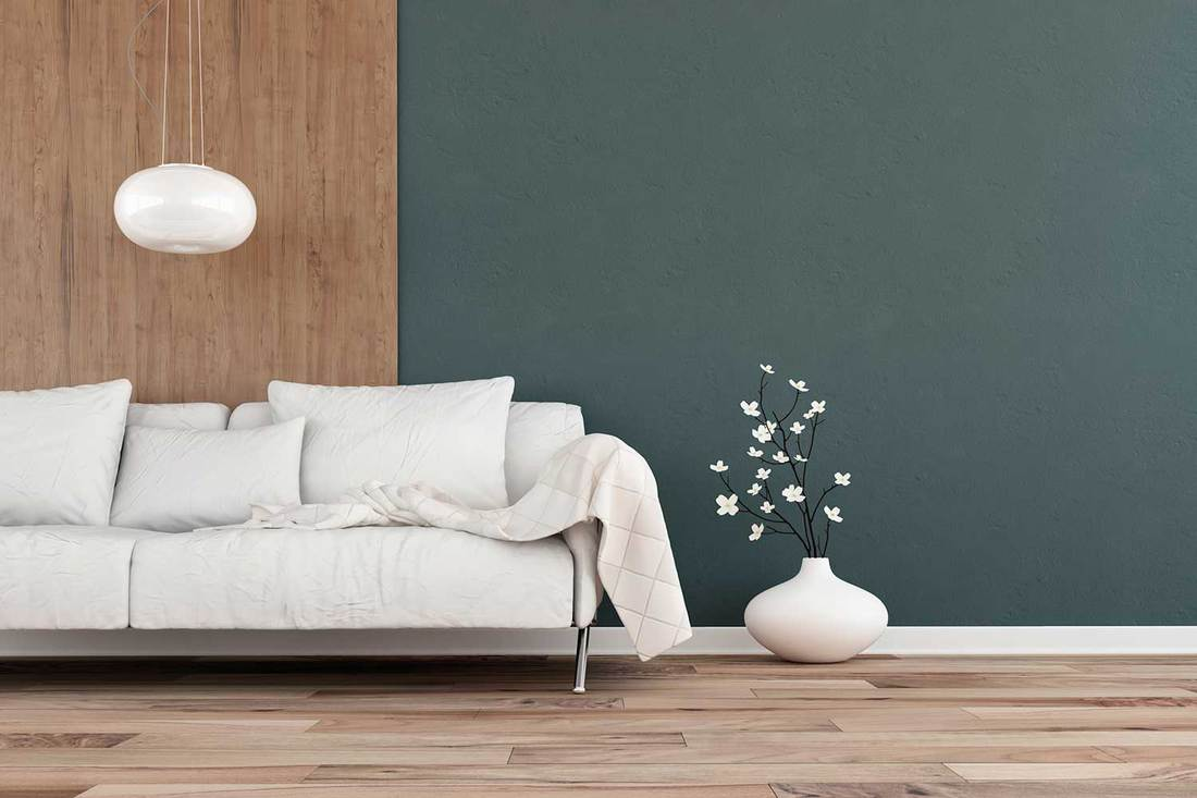 Elegant living room with white sofa on one side on hardwood floor in front of dark musk green plaster and hardwood wall
