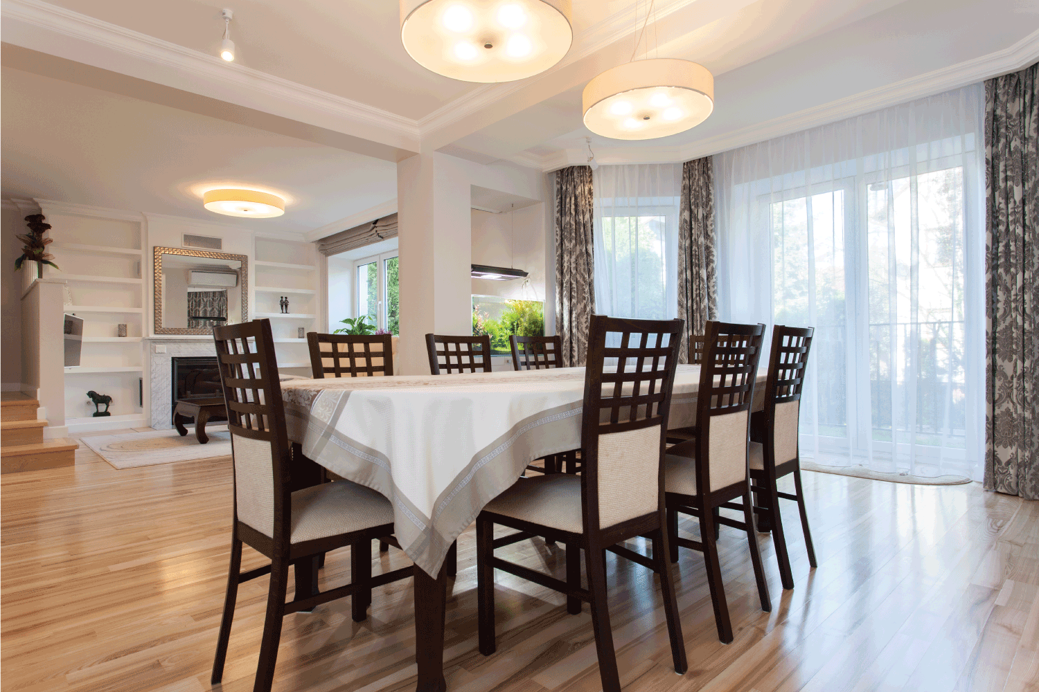 Elegant prepared table in stylish dining room with light colored tablecloth, light flowy curtains