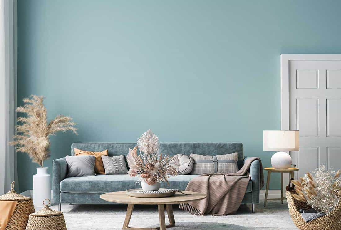Home interior mock-up with blue sofa, wooden table and decor in blue living room
