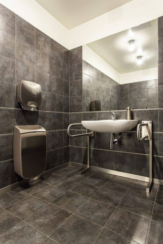 Interior of an ultra modern bathroom with gray tiled walls, a huge mirror, and modern fixtures