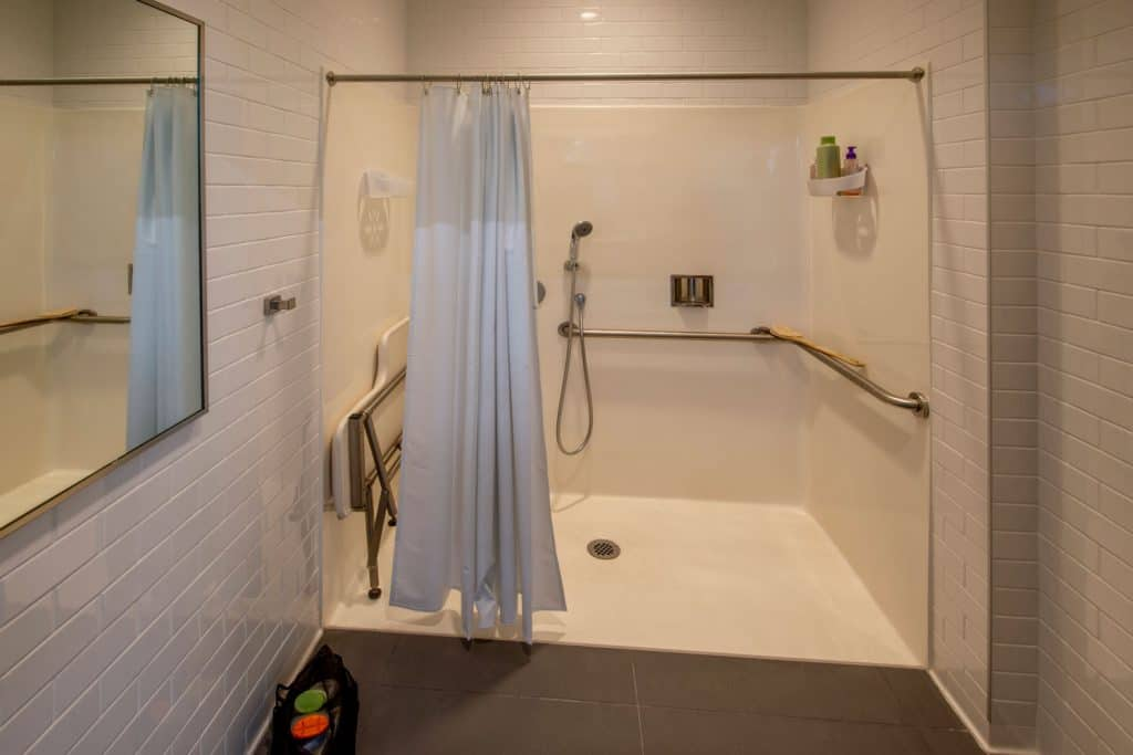 Interior of a narrow dark beige colored bathroom with a shower curtain walled shower area