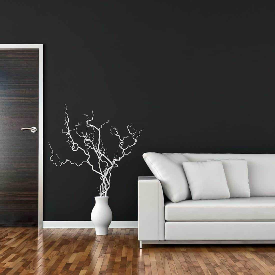 Living room with sofa and decoration on parquet floor in front of black plaster wall with a door